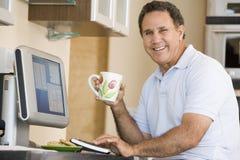 Homem na cozinha com sorriso do computador e do café Imagem de Stock