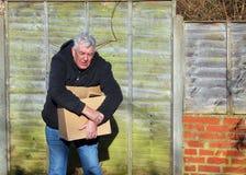 Homem na dor que leva a caixa pesada Tensão do pulso Fotografia de Stock Royalty Free