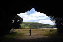 Homem na entrada dianteira da caverna Fotos de Stock