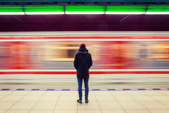Homem na estação de metro e em trem movente Foto de Stock