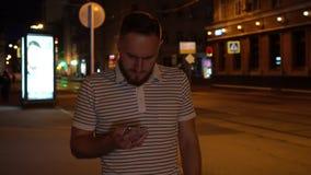Homem na estada da camisa listrada na rua e no olhar no telefone Surpreendido muito Indivíduo considerável farpado com telefone à filme