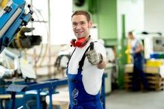 Homem na fábrica com polegar acima foto de stock