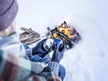 Homem na fogueira no inverno que tem a garrafa térmica com bebida imagens de stock