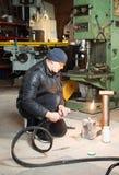 Homem na garagem, com soldadura de gás ardente da chama Imagens de Stock