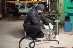 Homem na garagem, com soldadura de gás ardente da chama Foto de Stock