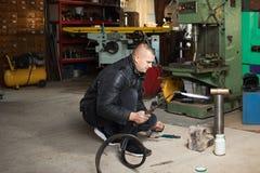 Homem na garagem, com soldadura de gás ardente da chama Foto de Stock Royalty Free