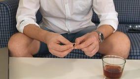Homem na garrafa do assistente com álcool, no anel de noivado esquerdo pensa, divórcio Close-up video estoque