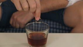 Homem na garrafa do assistente com álcool, no anel de noivado esquerdo pensa, divórcio Close-up filme