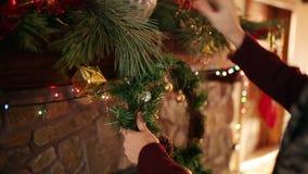 Homem na grinalda de suspensão kniited do Natal da camiseta acima da chaminé autêntica de pedra decorada com a festão de piscamen vídeos de arquivo