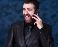 Homem na gritaria do terno de negócio em seu telefone celular Imagem de Stock