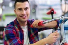 Homem na loja da bicicleta Fotos de Stock Royalty Free