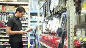 Homem na loja da eletrônica que escolhe bens no departamento do hardware filme