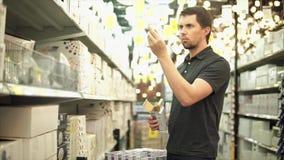 Homem na loja de ferragens com a caixa do pacote da lâmpada do diodo emissor de luz em suas mãos vídeos de arquivo
