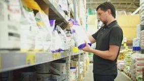 Homem na loja do hardware que escolhe um saco do emplastro da gipsita para a renovação home filme
