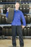 Homem na loja do pneu com um pneu Fotografia de Stock Royalty Free