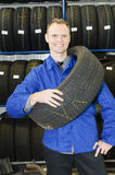 Homem na loja do pneu com um pneu Imagem de Stock Royalty Free