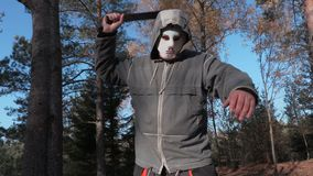 Homem na máscara assustador de Dia das Bruxas usando o machete filme
