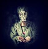 Homem na máscara de gás que guarda a flor nas palmas fotos de stock royalty free