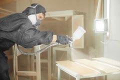 Homem na máscara do respirador que pinta pranchas de madeira na oficina Fotografia de Stock
