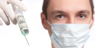 Homem na máscara que aponta com o close up da seringa do dinheiro Imagens de Stock