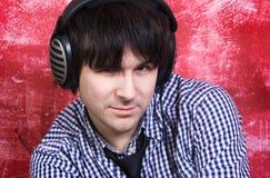 Homem na música de escuta dos auscultadores fotografia de stock