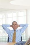 Homem na mesa com mãos atrás de sua cabeça Imagem de Stock