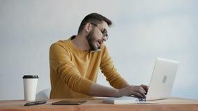 Homem na moda que datilografa um relatório e que fala no telefone vídeos de arquivo