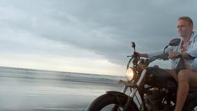 Homem na motocicleta de montada na praia velomotor do vintage no por do sol da praia em Bali Homem novo do moderno que aprecia a  video estoque
