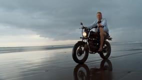 Homem na motocicleta de montada na praia velomotor do vintage no por do sol da praia em Bali Homem novo do moderno que aprecia a  filme