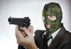 Homem na máscara da camuflagem com uma pistola Fotos de Stock