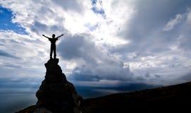 Homem na parte superior de uma rocha imagem de stock