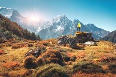 Homem na pedra e montanhas no por do sol em Nepal Imagem de Stock