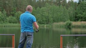 Homem na pesca azul do t-shirt na costa do rio video estoque