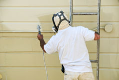 Homem na pintura da escada com injetor de pulverizador Foto de Stock Royalty Free