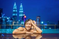 Homem na piscina exterior com opinião da cidade no céu azul fotografia de stock
