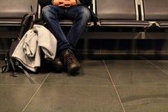 Homem na pose de espera que senta-se na cadeira com a trouxa no aeroporto Conceito da espera e da partida Imagens de Stock