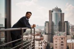 Homem na posição do terno do escritório no balcão imagem de stock royalty free