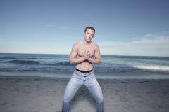Homem na praia com as mãos clasped foto de stock royalty free