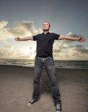 Homem na praia com os braços estendidos Fotos de Stock