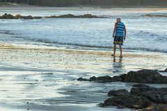 Homem na praia no nascer do sol que procura shell Imagens de Stock Royalty Free