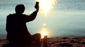 Homem na praia que fala no telefone celular video estoque