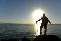 Homem na rocha litoral no nascer do sol Fotografia de Stock