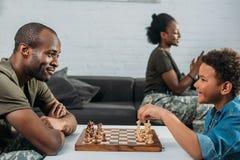 Homem na roupa da camuflagem que joga a xadrez com seu filho quando mãe e filha imagens de stock royalty free
