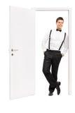 Homem na roupa elegante que levanta por uma porta aberta Imagens de Stock Royalty Free
