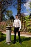 Homem na roupa, na coluna e no relógio de sol de Vicorian no parque fotografia de stock