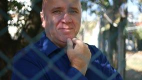 Homem na rua para trás de uma cerca metálica Looking à câmera e do sorriso feliz video estoque