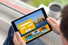 Homem na rua que guarda o tablet pc com reserva de hotel do app imagem de stock royalty free