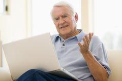 Homem na sala de visitas com portátil Fotografia de Stock Royalty Free