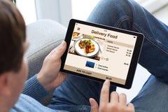 Homem nas calças de brim que guardam o tablet pc com a tela do alimento da entrega imagem de stock royalty free