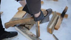 Homem nas luvas com um machado que desbasta a madeira desajeitadamente das placas no inverno filme